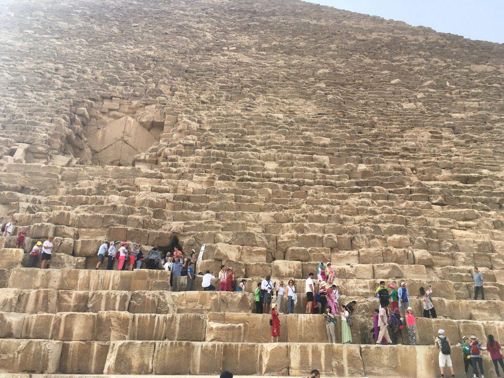 crowds climbing the pyramids